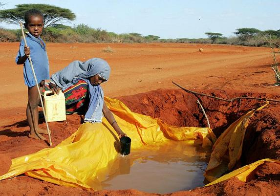 Kenyan woman fetches water using a plastic container on the road between Wajir and Garissa